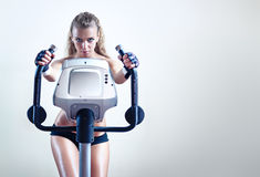 Young woman on exercise bicycle Royalty Free Stock Photos
