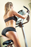 Young woman on exercise bicycle Royalty Free Stock Image
