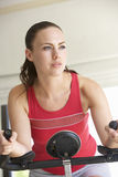 Young Woman On Exercise Bike Stock Photo