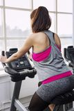 Young woman on exercise bike in the gym, view from the back stock image