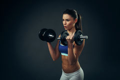Young woman exercise with dumbbells on dark background Royalty Free Stock Image