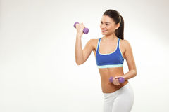 Young woman exercise with dumbbells on white backgroun Stock Photos