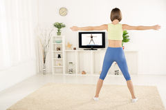 Young Woman Exercise In Front Of TV Royalty Free Stock Photos