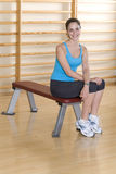 Young woman on exercise horse in gym, smiling, portrait Stock Photography