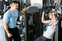 Young woman exercise on shoulder press machine Stock Photos