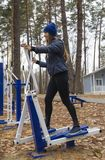 Young woman, exercise on a sports similator, nature, autumn, lifestyle, forest. Young woman doing exercises on a sports similator in the fresh air. Outdoor.The royalty free stock photo