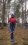 Young woman, exercise on a sports similator, nature, autumn, lifestyle, forest. Young woman doing exercises on a sports similator in the fresh air. Outdoor.The stock image