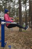 Young woman, exercise on a sports similator, nature, autumn, lifestyle, forest. Young woman doing exercises on a sports similator in the fresh air. Outdoor.The royalty free stock photos