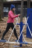 Young woman, exercise on a sports similator, nature, autumn, lifestyle, forest. Young woman doing exercises on a sports similator in the fresh air. Outdoor.The stock photos