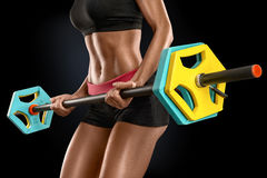 Young woman exercises with barbell  over black backgroun. Closeup of beautiful fitness woman preparing to lift some heavy weights. Beautiful young woman Royalty Free Stock Image
