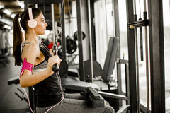 Young woman exercises on an exercise machine at the gym listenin. G to music Stock Image