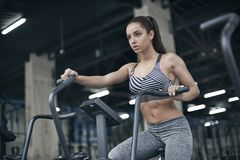 Young woman exercises in gym healthy lifestyle cardio workout on bike Stock Photo