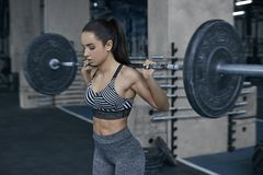 Young woman exercises in gym healthy lifestyle holding barbell Royalty Free Stock Photos