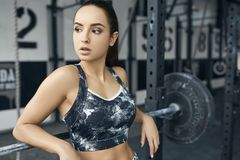 Young woman exercises in gym healthy lifestyle pulling weights Royalty Free Stock Photos