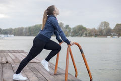 A young woman exercises by the river Royalty Free Stock Photo