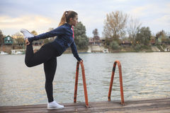 A young woman exercises by the river Stock Photo