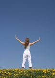 Young woman exercising. Outdoors in flowering dandelion field Stock Images