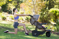 Young woman exercising with baby stroller. In park Stock Photo