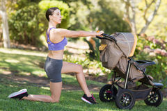 Young woman exercising with baby stroller. In park Royalty Free Stock Photos