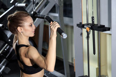 Young Woman Exercising Back On Machine In The Gym And Flexing Muscles. Muscular Athletic Bodybuilder Fitness Model stock images