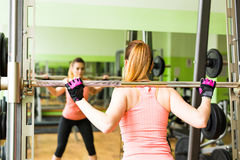 Young woman exercising with barbell in gym Stock Image