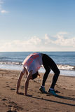Young woman exercising on beach. Young woman in crab posture on beach wearing black tights and white top with pink letters on it Stock Photo
