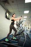 Young woman exercising on cardio machines in gym Royalty Free Stock Images