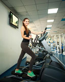 Young woman exercising on cardio machines in gym Stock Photo