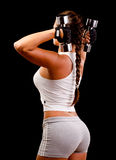 Young woman exercising with dumbbells. Beautiful young woman exercising with dumbbells isolated on black Stock Images