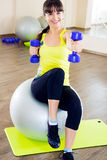Young woman exercising with dumbbells and fitball Stock Photos