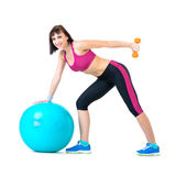 Young woman exercising with dumbbells on a fitness ball Royalty Free Stock Photo