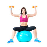 Young woman exercising with dumbbells on a fitness ball Stock Photography