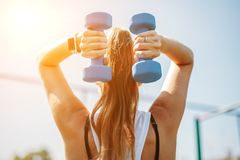 Young woman exercising with dumbbells. Healthy lifestyle concept. view from the back stock images