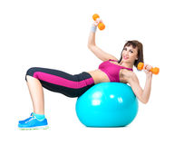 Young woman exercising with dumbbells laying on a fitness ball Royalty Free Stock Images