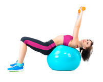 Young woman exercising with dumbbells laying on a fitness ball Royalty Free Stock Photo
