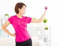 young woman exercising with dumbbells in living room Stock Photo