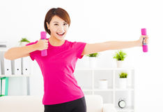Young woman exercising with dumbbells in living room. Happy young woman exercising with dumbbells in living room Stock Photos
