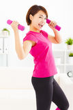 Young woman exercising with dumbbells in living room Royalty Free Stock Photos