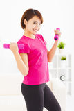 Young woman exercising with dumbbells in living room. Happy young woman exercising with dumbbells in living room Stock Images