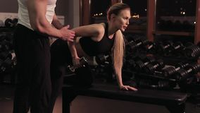 Young woman exercising with dumbbells under the supervision of a fitness trainer stock video