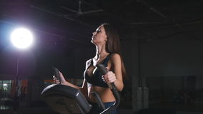 Young woman exercising on elliptical machine. In gym stock footage