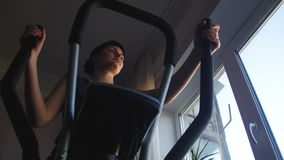 Young Woman Exercising on Elliptical Machine at Home on Against the Window stock video footage