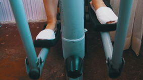 Young Woman Exercising on Elliptical Machine at Home. Sport woman is engaged in sports at home. Girl on the Elliptical Trainer. Home fitness stock footage