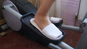 Young Woman Exercising on Elliptical Machine at Home stock footage