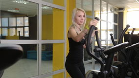 Young woman exercising on elliptical trainer. In gym stock footage