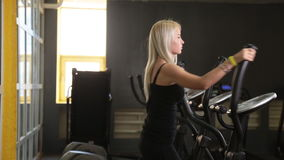 Young woman exercising on elliptical trainer. In gym stock video footage