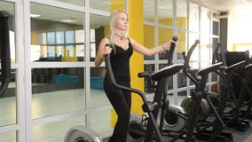 Young woman exercising on elliptical trainer. In gym stock video