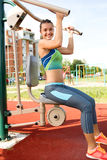Young woman exercising with exercise equipment in the public par Stock Photo