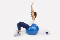 Young Woman Exercising On Fitness Ball Stock Image