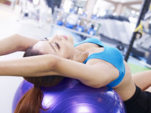 Young woman exercising with fitness ball. Young woman stretching her body on fitness ball in gym Royalty Free Stock Image